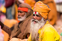 Hindu Sadhu holy man sitting in the street with his face painted and his colorful turban full of Holi colored powder, in Mathura Uttar Pradesh India