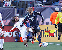 Sporting Kansas City defender Seth Sinovic (15) works to clear ball as New England Revolution forward Juan Toja (7) defends.  In a Major League Soccer (MLS) match, Sporting Kansas City (blue) tied the New England Revolution (white), 0-0, at Gillette Stadium on March 23, 2013.