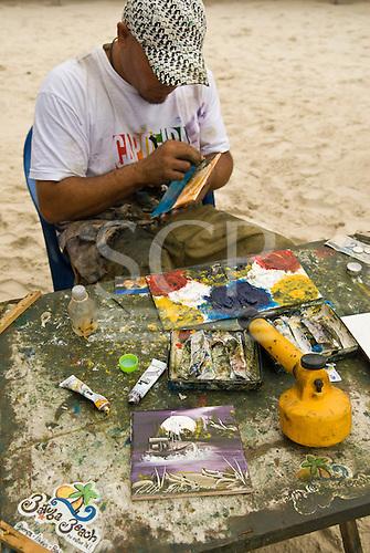 Ilheus, Bahia State, Brazil. Tourist resort south of Ilheus; beach artist painting scene on a ceramic tile.