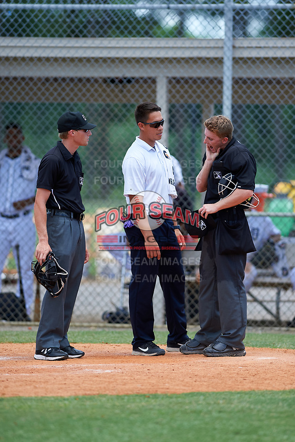GCL Tigers West trainer Manny Pena checks on home plate umpire Dylan Bradley as field umpire Tyler Witte looks on during a game against the GCL Pirates on July 17, 2017 at TigerTown in Lakeland, Florida.  GCL Tigers West defeated the GCL Pirates 7-4.  (Mike Janes/Four Seam Images)