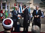 Israeli President Shimon Peres shakes the hand of U.S. President Barack Obama as Prime Minister Benjamin Netanyahu looks on during an official welcoming ceremony for the President at Ben Gurion International Airport near Tel Aviv Wednesday March 20, 2013. U.S. President Barack Obama arrived in Israel early Wednesday afternoon and was greeted by Prime Minister Benjamin Netanyahu, President Shimon Peres, and all of the ministers of Israel's recently formed government. Photo by Eyal Warshavsky.