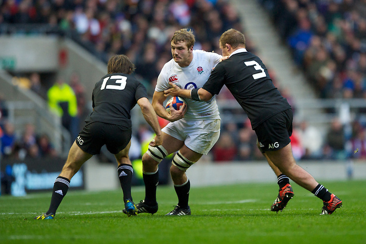 Joe Launchbury of England is tackled by Conrad Smith (left) and Owen Franks of New Zealand during the QBE Autumn International match between England and New Zealand at Twickenham on Saturday 01 December 2012 (Photo by Rob Munro)