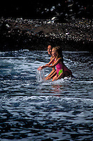 Two young girls playing at black sand beach