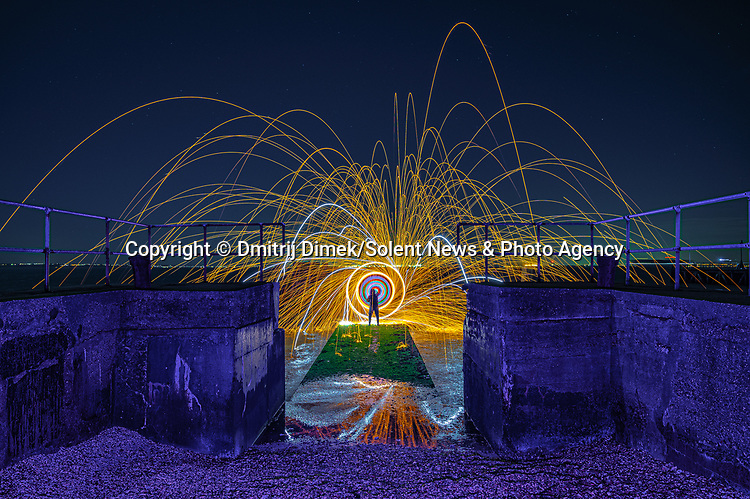 """Pictured:  Gunners Park in Shoeburyness, Essex.<br /> <br /> Amazing photos show sparks illuminating British landmarks as they fly from what appears to be a disc of colourful light.  This unique effect is the result of long-exposure night-time shots of a whisk stuffed with steel wool, which is set alight and spun at the end of a metal chain.<br /> <br /> Amateur photographer Dmitrij Dimek is passionate about what he calls 'light paintings', and took these photos at castles, beaches and other settings around Essex and London.  The 38 year old, who grew up in Poland but now lives in Southend-on-Sea, Essex, said: """"When I first found out about light painting with steel wool, I thought it was an outstanding way to connect with photography.  SEE OUR COPY FOR DETAILS.<br /> <br /> Please byline: Dmitrij Dimek/Solent News<br /> <br /> © Dmitrij Dimek/Solent News & Photo Agency<br /> UK +44 (0) 2380 458800"""