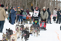Aaron Burmeister and team run past spectators on the bike/ski trail near University Lake with an Iditarider in the basket and a handler during the Anchorage, Alaska ceremonial start on Saturday, March 7 during the 2020 Iditarod race. Photo © 2020 by Ed Bennett/Bennett Images LLC
