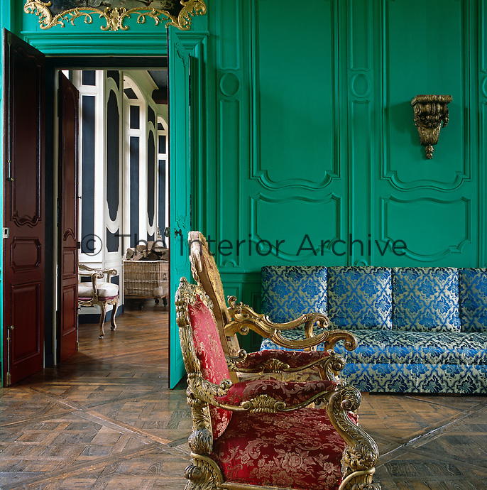 The Green Salon has a pair of gilded Louis XV chairs and a banquette upholstered in silver and blue antique damask
