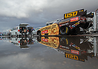 Feb 22, 2019; Chandler, AZ, USA; The car of NHRA funny car driver Jim Campbell reflects in a rain puddle as the car is towed to the staging lanes during qualifying for the Arizona Nationals at Wild Horse Pass Motorsports Park. Mandatory Credit: Mark J. Rebilas-USA TODAY Sports