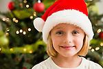 Smiling girl (6-7) wearing Santa hat
