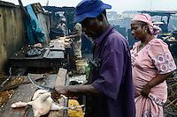 NIGERIA, Lagos, Arena Market , selling of live chicken which are immediately butchered here / Verkauf von lebenden Huehnern und Schlachtung vor Ort, Schlachter Lateef Jimoh