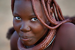 A young Himba woman with hair braids covered in ochre. Himba women cover their bodies with a traditional mixture of ochre and butter fat giving their skin and hair a reddish coloration. Himba are nomadic herders of goats and cattle, living in the dry desert regions of northwestern Namibia and southern Angola. [NO MODEL RELEASE]