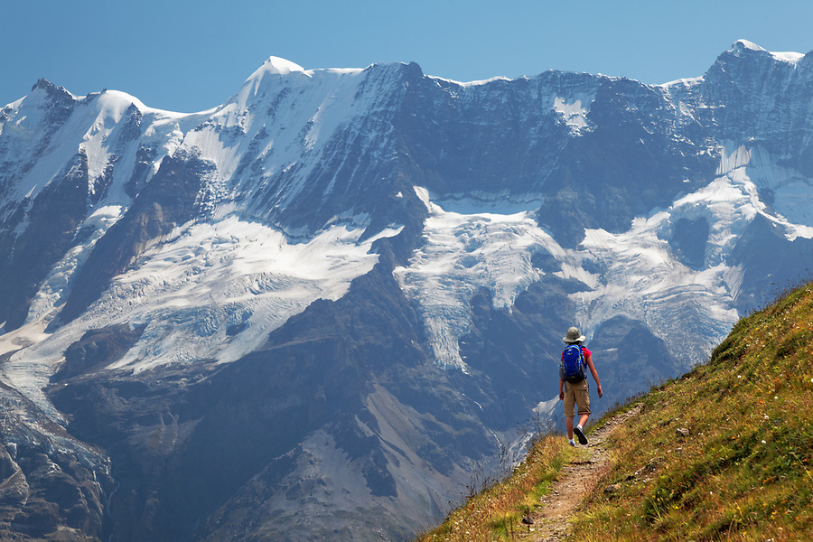 Girl hiking trail on trail from Grauseeli to Wasenegg ridge on Schilthorn mountain with the Lauterbrunnen Wall in background, Switzerland