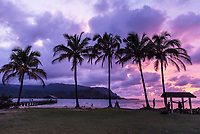 People enjoy the sunset from Hanalei Pier and the shoreline along Hanalei Bay, Kaua'i.