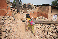 Sandha, 9, is climbing up through the rubble of her destroyed house at Dhulikhel, near Kathmandu, Nepal. May 8, 2015