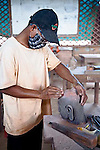 Cambodian young man with mask working on sculpture in handicraft workshop in Siem Reap