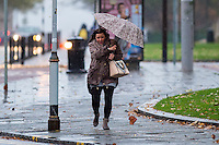 "Monday  21 November 2014<br /> Pictured: A woman is battered by the rain and wind as she walks along with an umbrella<br /> Re: A yellow ""be aware"" weather warning has been issued as widespread heavy rain hits the country. The Met Office said gusts of winds could hit 50mph (80km/h) with localised flooding and disruption to travel."