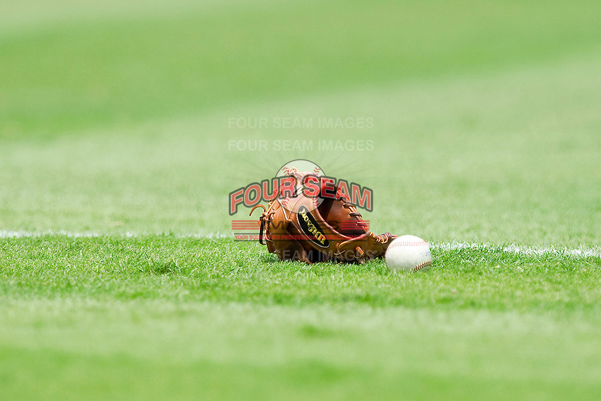 A baseball glove and ball sit in the grass down the left field line prior to the International League game between the Syracuse Chiefs and the Charlotte Knights at Knights Stadium on June 19, 2011 in Fort Mill, South Carolina.  The Knights defeated the Chiefs 10-9.    (Brian Westerholt / Four Seam Images)