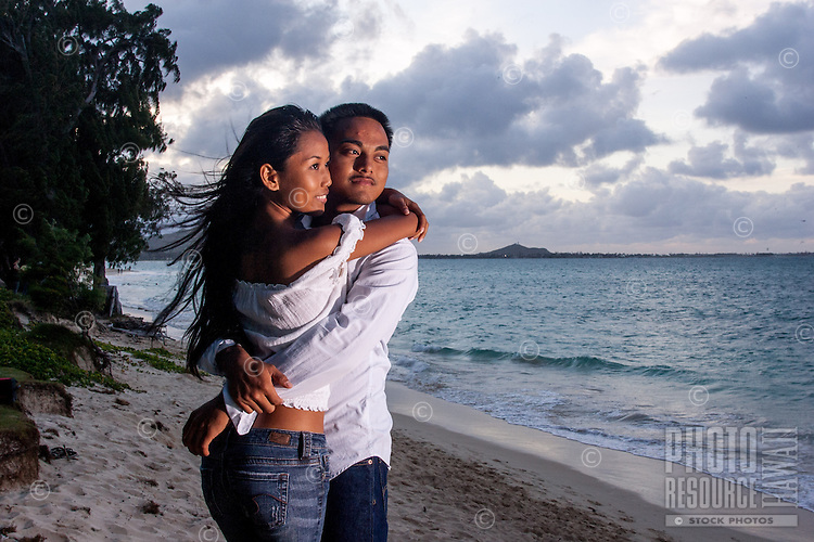 At sunset, a young, engaged local couple look out at the ocean at Lanikai Beach, Windward O'ahu.