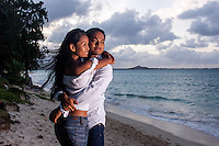 At sunset, a young, engaged local couple look out at the ocean at Lanikai Beach, Windward O'ahu.