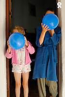 Boy and girl (7-12) blowing up balloons, wearing pyjamas (Licence this image exclusively with Getty: http://www.gettyimages.com/detail/sb10065474br-001 )