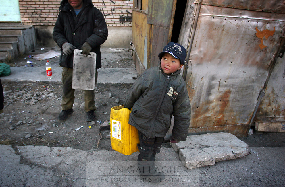 MONGOLIA. Ulaan Baatar. Huyga,6, prepares to go out and collect bottles and rubbish in order to sell to local recycling stations. As the global financial crisis grips Asia, Mongolia is feeling the implications first hand as the country suffers from rising inflation pushing the price of food and fuel ever upwards. For the country's homeless, who live in sewers and abandoned garages in the capital and already face extreme discrimination and are denied access to basic health and social care, their lives are hanging in the balance. 2008