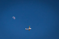 A single engine private plane below and to the right of the waxing gibbous moon in a clear blue summer sky.