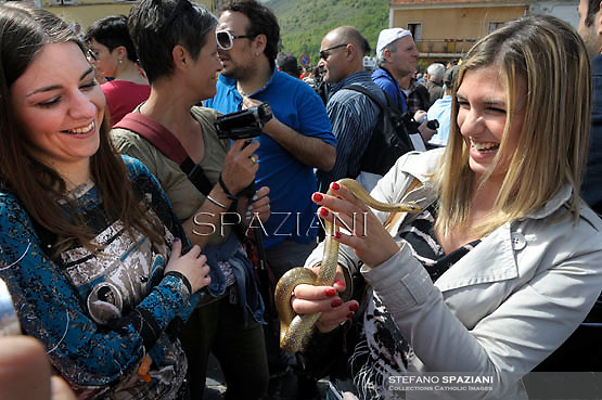 """A girl holds a snake during an annual procession dedicated to Saint Domenico, in the streets of Cocullo, in the Abruzzo region, on May 1, 2012.....The St. Domenico's procession in Cocullo, central Italy. Every year on the first  of May, snakes are placed onto the statue of St. Domenico and then the statue is carried in a procession through the town. St. Domenico is believed to be the patron saint for people who have been bitten by snakes:..Italy, Cocullo, in the Province of L'A...quila, is at 870 meters a.s.l., along the railway line connecting Sulmona to Rome. The village rises alongside Mount Luparo (1327 meters) """"The valley opening in front of the village is surrounded by bare rocks, while on the other side, to the south, snow-capped mountain crests follow one after the other..."""".San Domenico Abate lived in the 10th and 11th centuries AD. Born in Foligno, in the Umbria region, he started his pilgrimages, preaching and ascetic practices in Central Italy, making miracles recorded by the word-of-mouth tradition. He died on 22 January 1031 and was buried in Sora...Cocullo snake charmers are over with their snake hunting. They proceeded through the During the procession on the first in May, before the snakes are placed all over the statue of St. Dominick, they will be fed with milk kept in containers with crusca. It is the snake that, most of all other elements, expresses an ancestral myth: the unknown aspect and unpredictability of the natural environment with man's innate need to achieve the dominance on his own habitat. ..Snakes and wolves were the emblems of Italic peoples like the Marsians and Irpinians. Some areas in Abruzzo, especially in the Sagittario valley, were under the menace of wolves and snakes, which for the local populations represented the uncertainty and anxiety of their existence that, together with the precariousness and hardships of life, were almost unbearable. Therefore the community adopted such magical-religious rites (namely the snakes enve"""