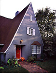 One story gray house with windows, chimney, front door, path, and front lawn.