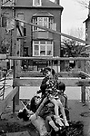 Chiswick Women's Aid, chiswick London Uk 1975. exterior back garden, children playing together.