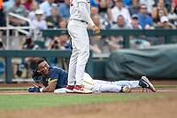 Michigan Wolverines designated hitter Jordan Nwogu (42) after sliding into third base during Game 6 of the NCAA College World Series against the Florida State Seminoles on June 17, 2019 at TD Ameritrade Park in Omaha, Nebraska. Michigan defeated Florida State 2-0. (Andrew Woolley/Four Seam Images)