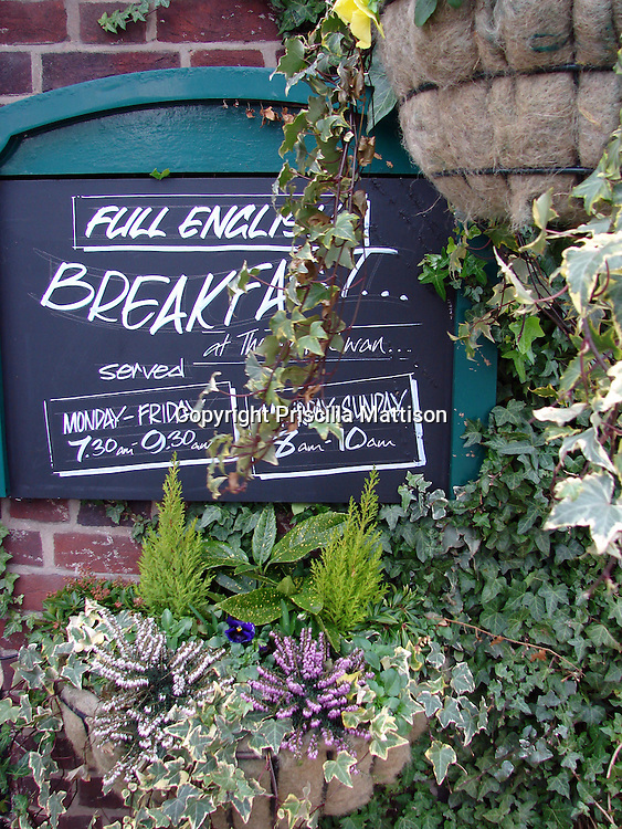 """Cotswolds, England - February 3, 2008:  Ivy partly obscures the """"Full English Breakfast"""" sign on the exterior of a restaurant."""