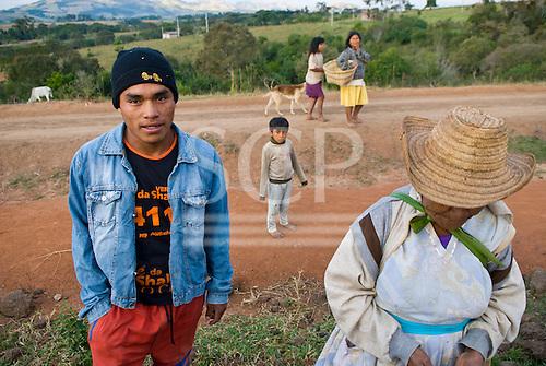 Parana State, Brazil. Kaigang Indian reserve of Faxinal de Catanduva. Young Kaingang man with his grandmother and other Kaingang people.