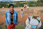 Parana State, Brazil. Kaigang Indian reserve of Faxinal de Catanduva. Young Kaingang man with his grandmother and other Kaingang people.