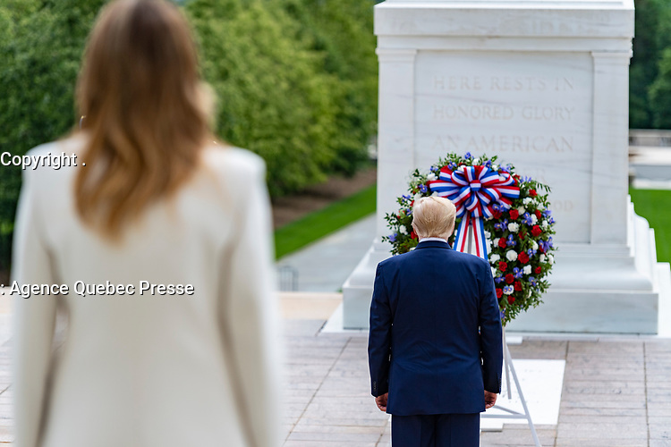 President Donald Trump observes a moment of silence during a Presidential Armed Forces Full Honors Wreath-Laying Ceremony in observance of Memorial Day at Arlington National Cemetery, Arlington, Virginia, May 25, 2020. This was the 152nd Memorial Day wreath-laying and observance ceremony at Arlington National Cemetery. Pictured forward is First Lady Melania Trump. (U.S. Army photo by Elizabeth Fraser / Arlington National Cemetery / released)