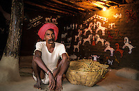 INDIEN Dhar Distrikt , Adivasi , Ureinwohner Indiens , Bhil Mann mit Sorghum Korb in seiner Huette mit traditioneller Wandbemalung / INDIA Dhar , Adivasi , the tribal people of India , Bhil man with Sorghum basket in his hut with traditional wall painting