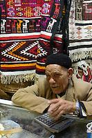 Tripoli, Libya - Rug and Souvenir Vendor in the Medina (Old City).  He wears a black Tunisian chechia, a cap popular in Libya.