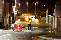 Pictured: A police officer stands in the flooded closed off Old Station Road in Carmarthen, Wales, UK. Saturday 13 October 2018<br /> Re: River Towy has burst its banks and adjacent properties have flooded, caused by storm Callum, in Carmarthen, west Wales, UK.