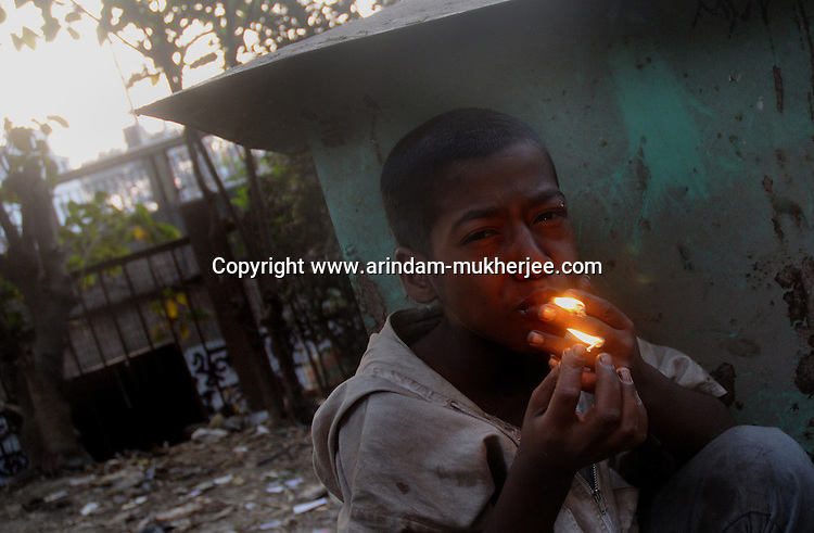 Alamgir lights up a cigarette. He is a run away kid staying at Sealdah station and addicted to drugs. He is staying Sealdah station for last 6 years from the time he ran away from his home due to domestic violence and poverty. As per his version his father was a drunkard and used to beat his mother for no reason. His father even could not earn enough money to buy food for their big family. Due to this traumatic situation he ran away from house at the age of seven. Ever since, the Sealdah railway station in Kolkata has been his home. As far as company is concerned, he had not much reason to miss his family. There are around 500 children, from 5 to 16 years, who live in the premises of Kolkata's second largest train terminus. Most of them addicted to Brown Sugar and sniffing industrial adhesive Dendrite. They say they don't feel hungry if they take the drugs. Their presence is conspicuous, even in a place that registers an average footfall of 1.4 million on weekdays. Their activities cover a wide range, from begging, to pulling handcarts, to petty theft, to selling odds and ends on the platform or on trains. The money, earned or ill-gotten as the case may be, is spent in procuring heroin, brown sugar, cocaine, and tubes of Dendrite. Calcutta, West Bengal, India. Arindam Mukherjee