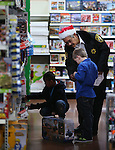 Carson City Sheriff's Office Volunteer James Matsuoka helps two of nearly 170 elementary students shop as part of the Holiday with a Hero program at Walmart in Carson City, Nev., on Tuesday, Dec. 17, 2013. The community event partners military, firefighters, law enforcement and medical personnel with local Students in Transition to provide them with Christmas presents.<br /> Photo by Cathleen Allison