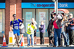 © Joel Goodman - 07973 332324 . 20/09/2015 . Stockport , UK . A woman in the watching crowd cheers winner JAKE LITTLEHALES (23 from Stockport ) as he rounds the corner for the final stretch of the race . The Big Stockport run from St Petersage in Stockport Town Centre . Photo credit : Joel Goodman