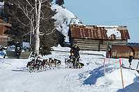 Nathan Schroeder runs down the road into the Nulato checkpoint on Saturday afternoon March 12th during the 2016 Iditarod.  Alaska    <br /> <br /> Photo by Jeff Schultz (C) 2016  ALL RIGHTS RESERVED