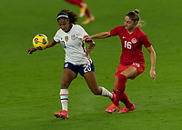 ORLANDO CITY, FL - FEBRUARY 18: Margaret Purce #20 turns away from the pressure by Janine Beckie #16 during a game between Canada and USWNT at Exploria stadium on February 18, 2021 in Orlando City, Florida.