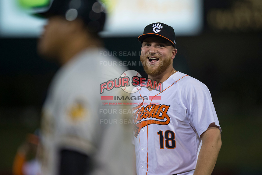 Fresno Grizzlies first baseman AJ Reed (18) talks to the Salt Lake Bees first base coach Ray Olmedo (4) during a Pacific Coast League game against the Salt Lake Bees at Chukchansi Park on May 14, 2018 in Fresno, California. Fresno defeated Salt Lake 4-3. (Zachary Lucy/Four Seam Images)