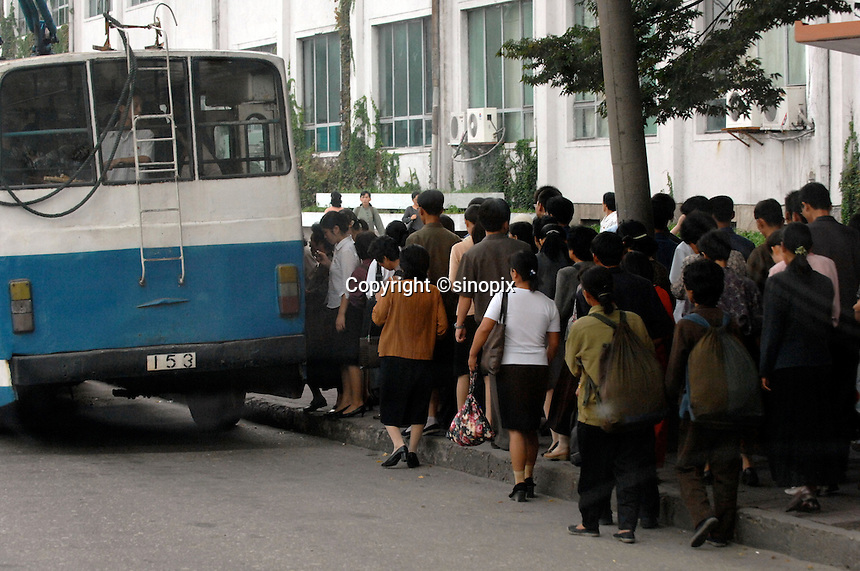 People queue to get on a packed trolley bus on the streets of Pyongyang, North Korea.