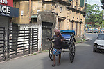A rickshaw puller roams around a locality to fnd a customer. Due to lockdown because of Corona Virus these migrant workers are one of the most econoimically affected people.  Kolkata, West Bengal, India. Arindam Mukherjee.