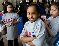 Local students change into t-shirts given to them during a US Soccer Foundation clinic held at City Center in Washington, DC.
