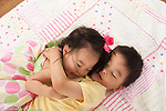 3 year old preschool age boy with 18 month old baby toddler sister, giving her a hug