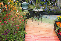 Colorful rainbow walkway path with hot colored flowers leading to cooler blue toned plants, with garden patio furniture, gazing ball