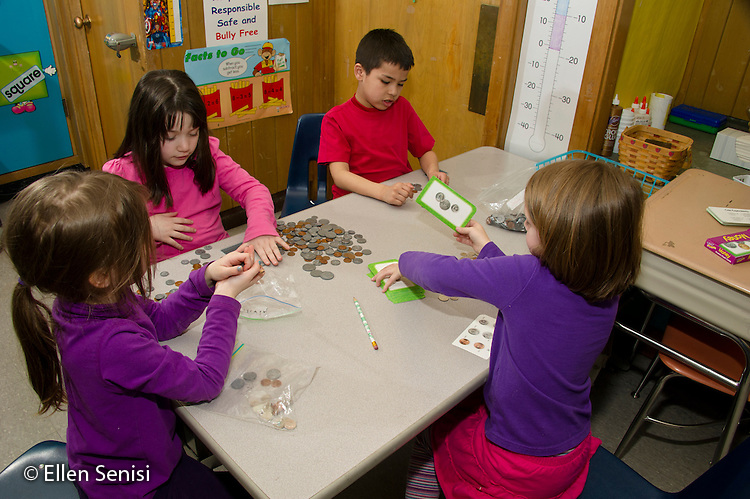 MR / Schenectady, New York. Paige Elementary School (urban public elementary school). First grade independent work at learning center time. Students in small group use play coins as they learn to count and use money. MR: AL-g1g. ID: AL-g1g. © Ellen B. Senisi.