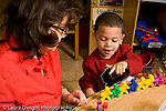 Education Preschool 3-5 year olds female teacher working with boy who is counting colored plastic connecting people figures horizontal