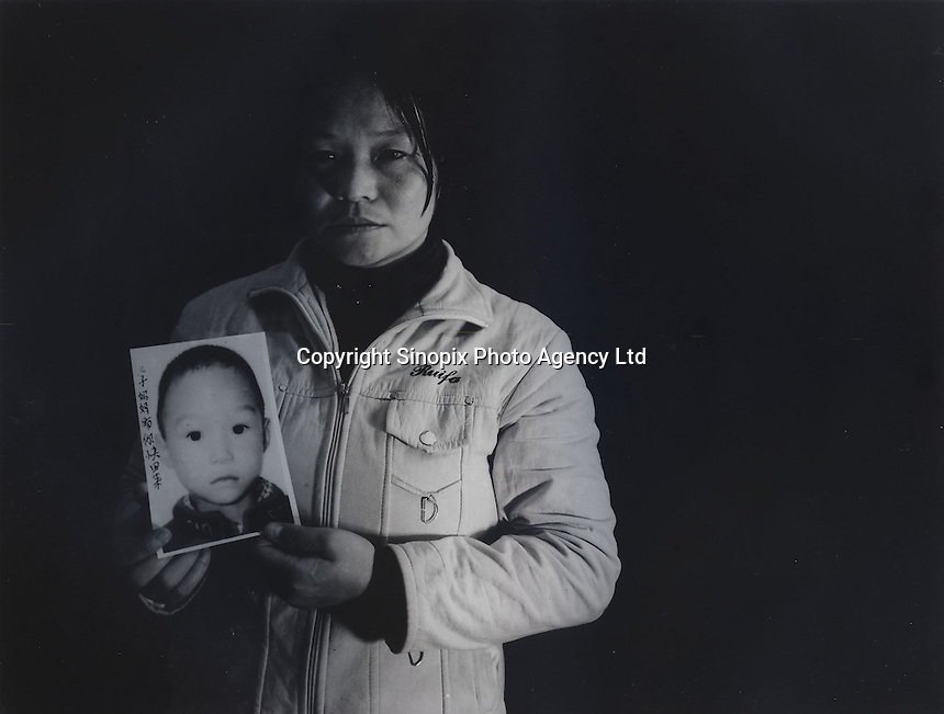 """Mrs Deng Yongmin, 31, holds a picture of her son Liu Lang, 5 years and 3 months, who was stolen in March 2003. The message reads """"My son, mummy hope you come back soon.""""..PHOTO BY SINOPIX"""
